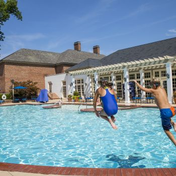 Kids cannon ball into pool