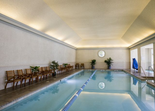 An empty indoor pool with chairs along one side.