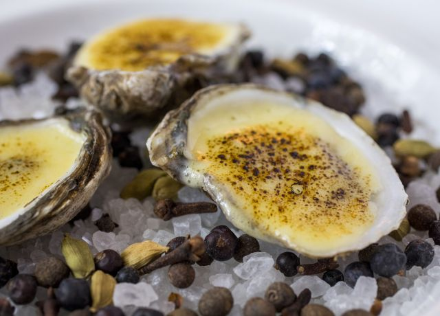 Three baked oysters are on a white plate filled with ice.
