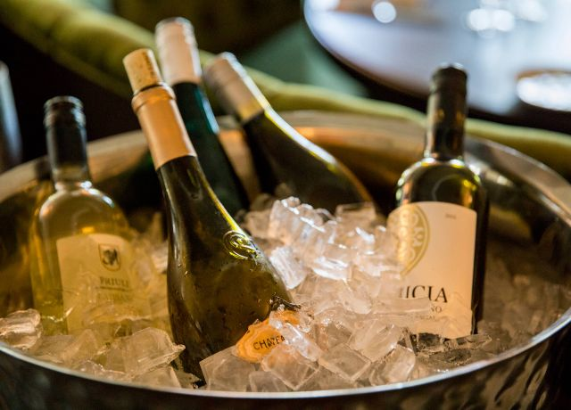 bottles of wine sit in a bucket of ice