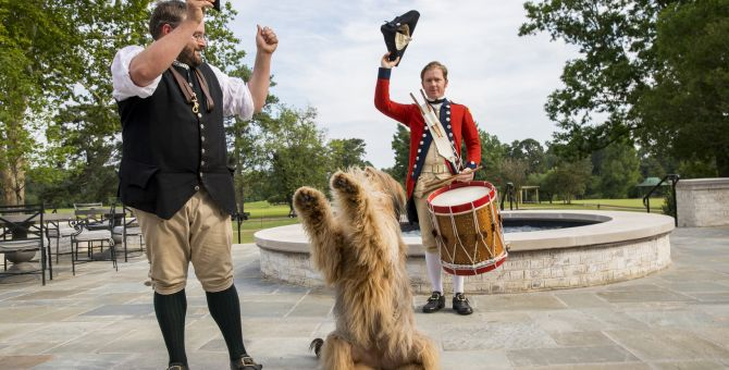 Soldiers in Colonial dress do tricks with dog at Colonial Williamsburg, VA