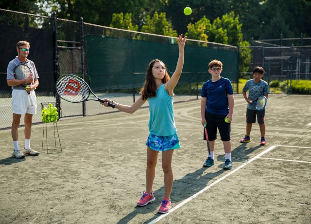 Children learning to play tennis on a tennis court.