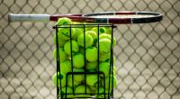 tennis racket sits on top of basket of tennis balls