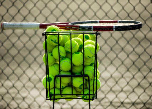 tennis racket sits on top of basket of tennis balls