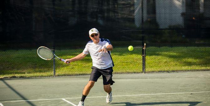 man swings racket at tennis ball