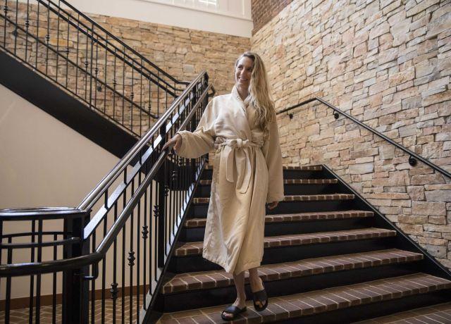 woman walks down staircase at spa
