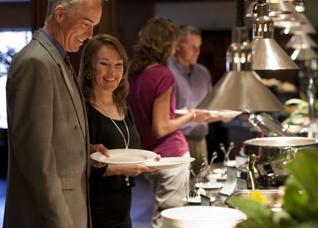 A man and woman stand at a buffet holding plates