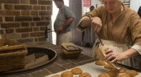 A baker at Raleigh Tavern Bakery packages up gingerbread cookies