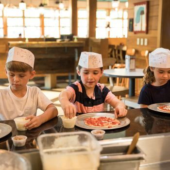 Children construct pizzas at Huzzahs Eatery