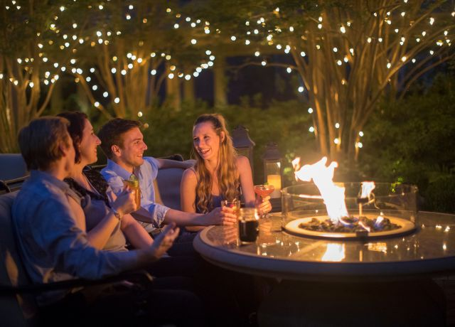 Couples relax by a fire pit