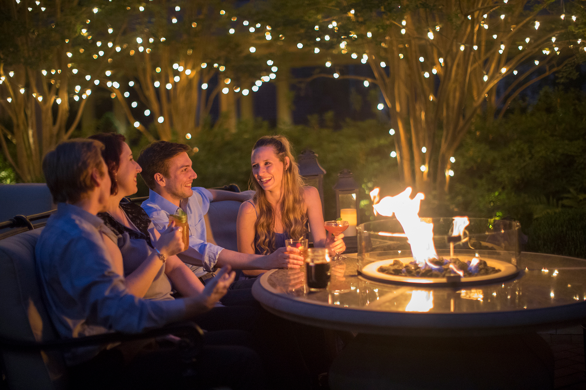 Couples socializing with drinks around fire pit