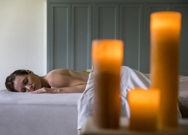 Woman at spa receives massage with candles in foreground