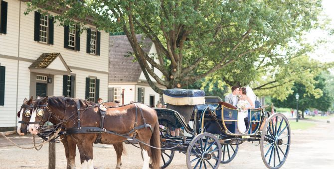 A couple on their wedding day sitting in a horse and buggy.