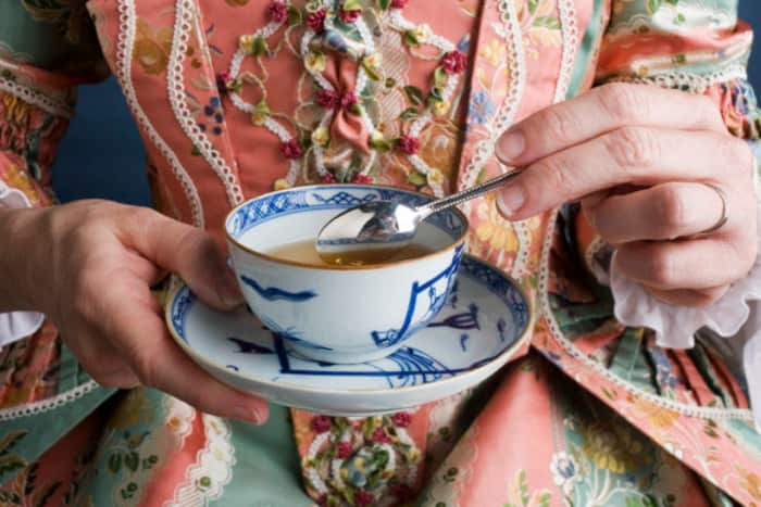 A woman in colonial garb stirs a cup of tea.