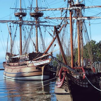 Two historic ships docked in the water.