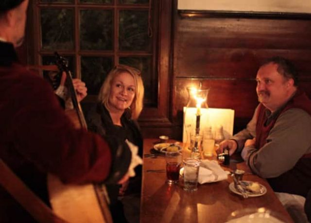 A couple listen to a musician playing guitar at Chowning's Tavern at Colonial Williamsburg.