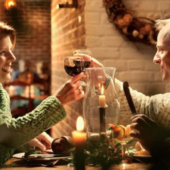 A couple toast with red wine over dinner at Shields Tavern in Colonial WIlliamsburg.