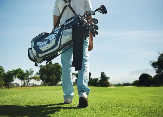 Golf man walking with shoulder bag on course in fairway