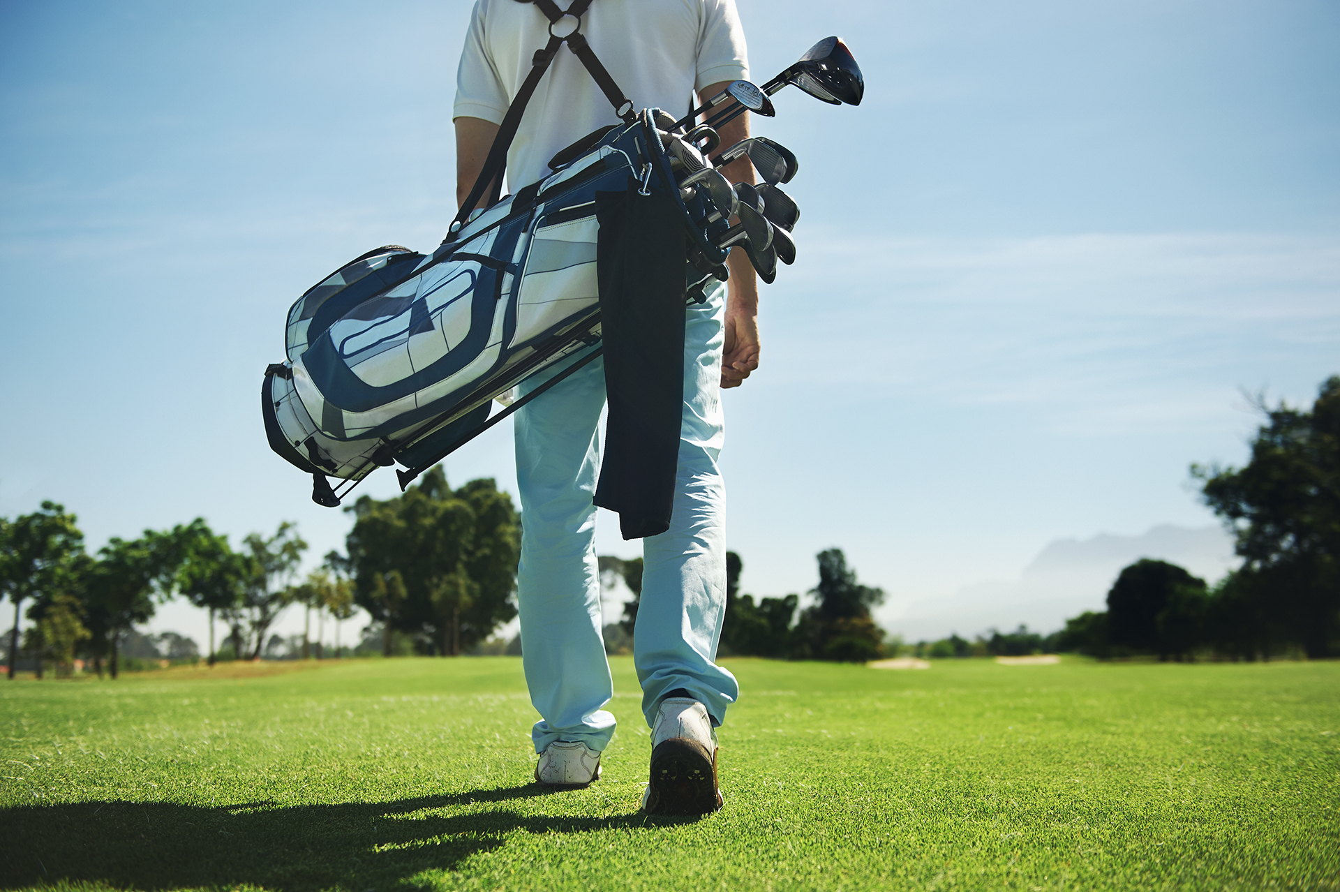 Man walking on golf course with clubs over his shoulder on a sunny day