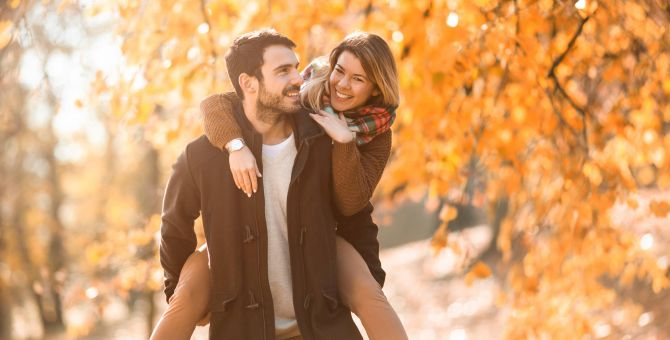 Man giving woman piggyback ride on fall day