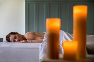 A woman on a massage table with candles in front
