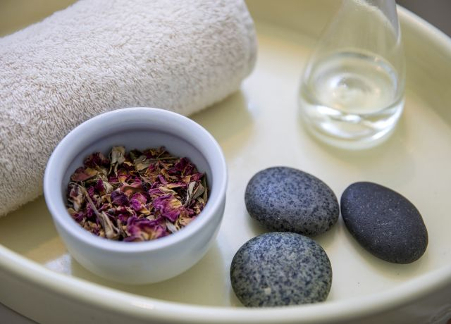 A tray in spa filled with a towel, potpourri, hot stones and a glass of water.
