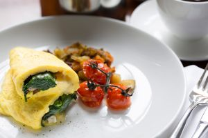 A plate with an omelette and tomatoes.