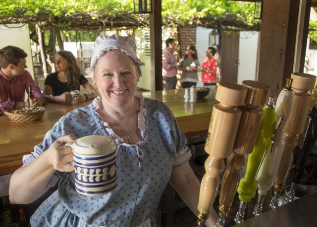 Woman in Colonial dress hold mug of beer with bar patrons in background