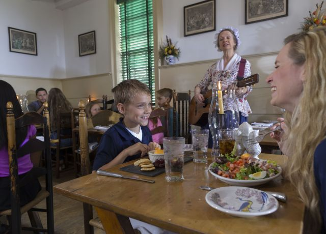 Woman in Colonial dress plays music while family enjoys meal