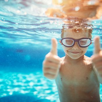 Happy little boy underwater gives thumbs up
