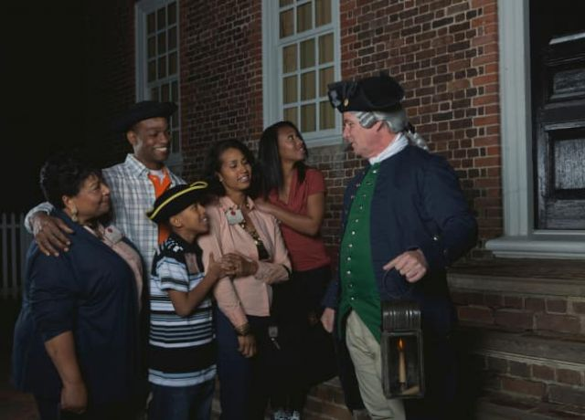 Family listens to historical stories from man in Colonial dress