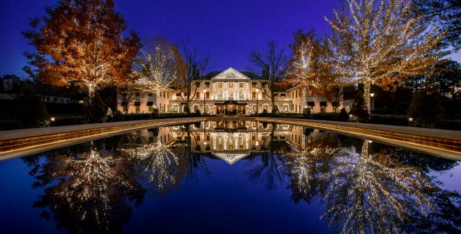 Williamsburg Inn with lights at night overlooking pond
