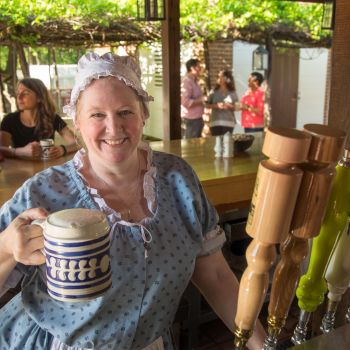 Woman in Colonial dress holds mug of beer with bar patrons in background
