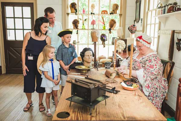 Curious family watches woman in colonial dress making wigs