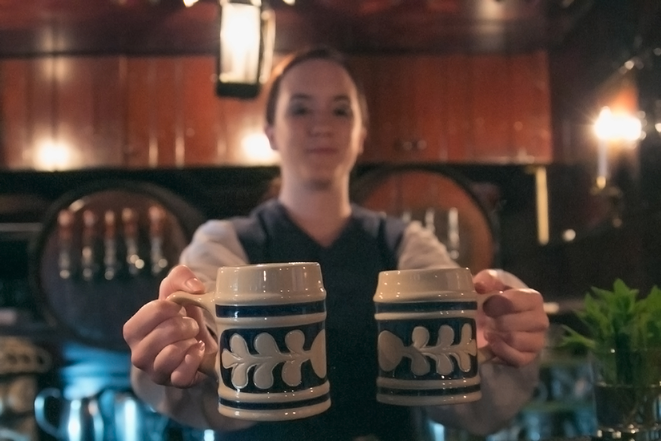 a woman holding two pint mugs