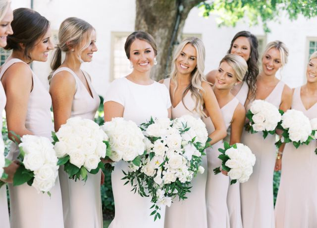Bridal party with a bride and eight bridesmaids, holding flowers
