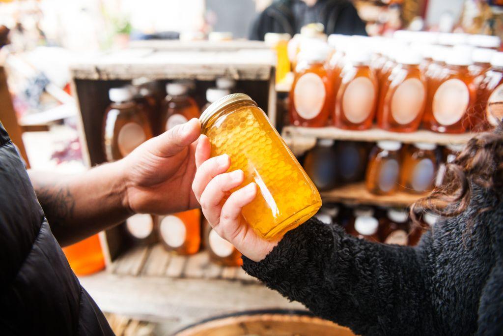picking up honey in jar